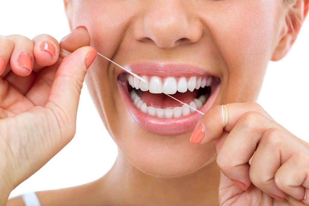 Lady-flossing-her-teeth-as-part-of-a-strong-oral-routine