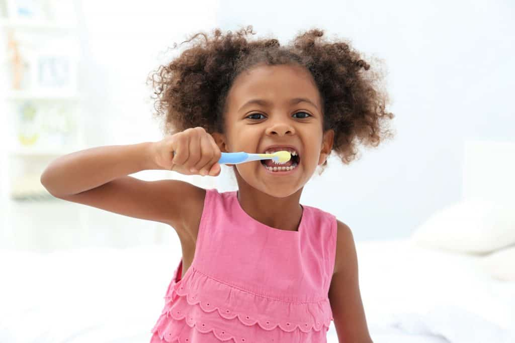 a child brushing her teeth as part a strong oral routine