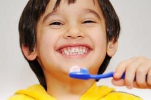 a smiling child brushing teeth